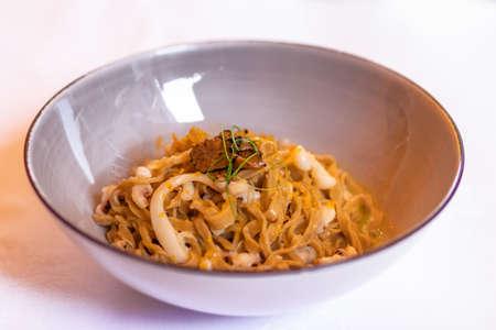 Delicious Italian buckwheat pasta (pasta di grano saraceno) with squid and truffle. Italian recipe. Selective focus.