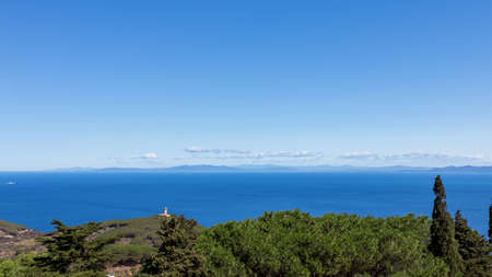 Seascape with a lighthouse in the foreground and Tuscany coastline on the horizon. Giglio Island (Isola del Giglio), Tuscany, Italy