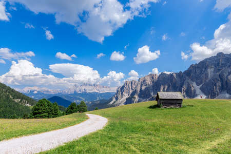 Rural road in green alpine valley with view of Italian Dolomites. Italian Alps, Corvara in Badia. Stok Fotoğraf