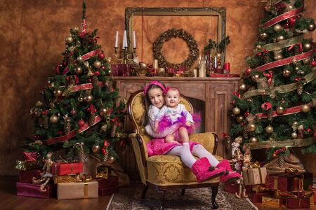 cintillos: Cute sisters sitting on armchair near christmas trees, wearing pink skirts and red headbands. Smiling toddlers. Christmas presents.