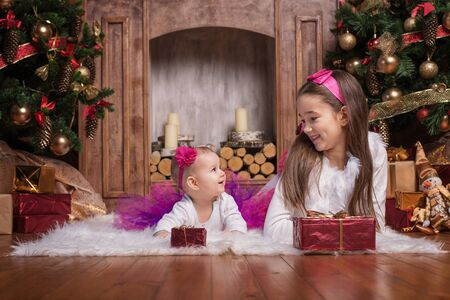 cintillos: Cute sisters lying on white carpet near christmas trees, wearing pink skirts and red headbands. Smiling toddlers. Christmas presents.