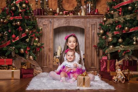 cintillos: hermanas linda que se sienta en la alfombra blanca cerca de los árboles de navidad, con faldas de color rosa y cintas rojas. Sonriendo niños pequeños. Regalos de Navidad.