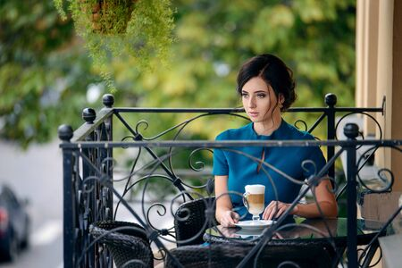 Pretty girl in classic elegant dress sitting on the terrace of the summer cafe going to drink coffee.