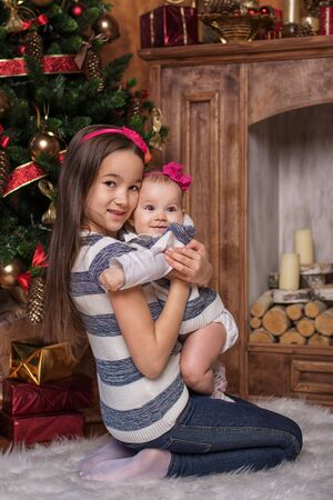 cintillos: Cute sisters sitting on white carpet near christmas tree and fireplace, wearing striped sweaters and red headbands. Smiling toddlers. Christmas gifts Foto de archivo