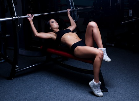 girl working out: Sexy sporty woman doing power fitness exercise at sport gym. Beautiful girl working out in gym