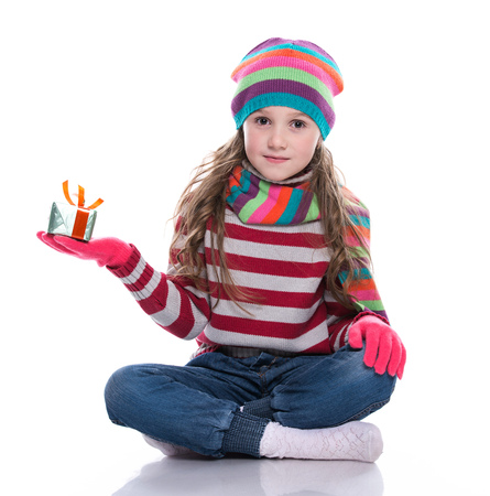 Smiling pretty little girl wearing coloful knitted scarf, hat and gloves, holding christmas gift isolated on white background. Winter clothes and christmas concept Stock Photo