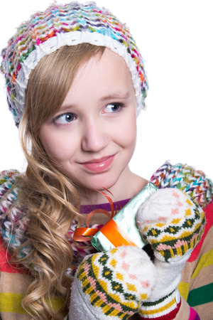Smiling pretty young girl wearing coloful knitted scarf, hat and mittens, holding christmas gift isolated on white background. Winter clothes and christmas concept
