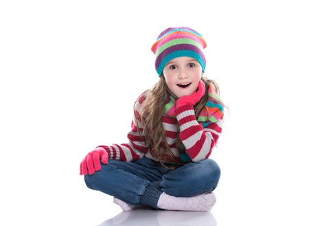 Smiling pretty little girl wearing colorful knitted scarf, hat and gloves isolated on white background. Winter clothes