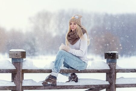 Attractive young blonde girl walking in winter forest. Pretty woman in wintertime outdoor. Wearing winter clothes. Knitted sweater, scarf, hat and mittens