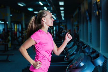 Attractive fitness girl running on machine treadmill. Pretty girl doing workout at modern fitness gym