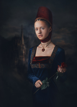 Portrait of a gorgeous girl in medieval era dress and headdress. Medallion in a shape of heart. Holding red rose in hands 스톡 콘텐츠