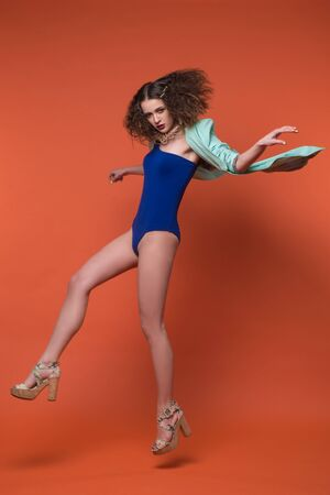 showgirl: Fashion photo of beautiful girl in studio. Young brunette woman in blue underwear and turquoise jacket posing on red background. Curly hairstyle. She is jumping and dancing