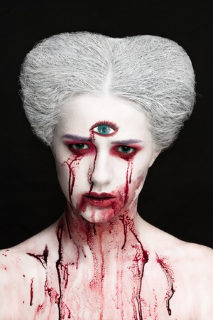 gore: Mysterious beauty portrait of snow queen covered with blood. Bright luxury makeup. Gore dripping from the mouth