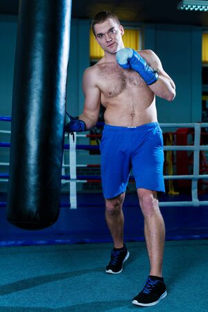 Handsome man in blue boxing gloves training on a punching bag in the gym. Male boxer doing workout Stock Photo