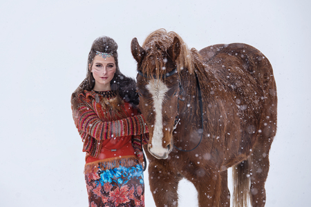 Native indian woman with traditional makeup and hairstyle in snowy winter. Beautiful girl in ethnic dress hugging a horse Stock Photo