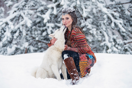 eskimo woman: Native indian woman with traditional makeup and hairstyle in snowy winter. Beautiful girl in ethnic dress hugging an eskimo dog Stock Photo