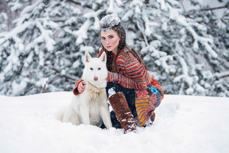 Native indian woman with traditional makeup and hairstyle in snowy winter. Beautiful girl in ethnic dress hugging an eskimo dog Stock Photo
