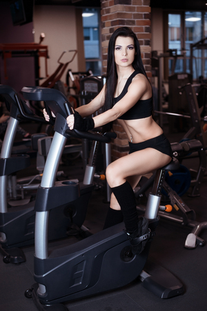 cardio workout: Muscular young woman wearing sportswear training on exercise bikes in gym. Intense cardio workout Stock Photo