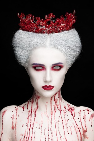 Mysterious beauty portrait of snow queen covered with blood. Bright luxury makeup. White demon eyes