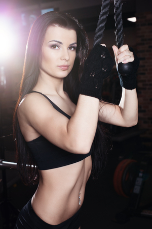 Muscular brunette fitness girl doing exercises in the gym. Fitness girl lifting weights on a machine for bodybuilders Stock Photo