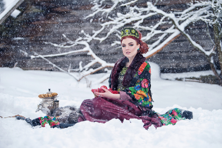 Portrait of a gorgeous young woman in russian style dress on a strong frost in a winter snowy day with apples and samovar. Russian model girl in traditional headdress