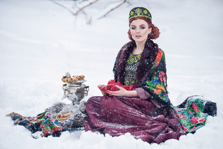 hoarfrost: Portrait of a gorgeous young woman in russian style dress on a strong frost in a winter snowy day with apples and samovar. Russian model girl in traditional headdress