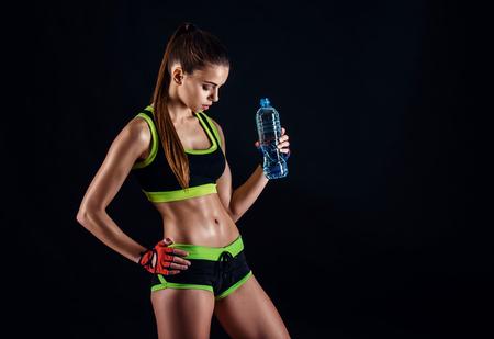 黒の背景にスタジオでボトルとスポーツウェアの若い運動の女性。理想的な女性のスポーツ図。完璧な彫刻が施された筋肉とタイトなボディとフィ