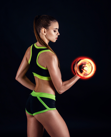 Young athletic woman in sportswear with fiery dumbbells in studio against black background. Ideal female sports figure. Fitness girl with perfect sculpted muscular and tight body