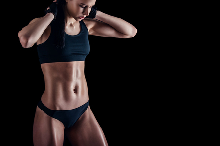 Sporty female with perfect body against black background. Fitness woman in sportswear with ideal fitness body