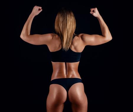 Muchacha deportiva con los grandes músculos en ropa de deportes negra. Tanned joven mujer atlética. Un gran cuerpo femenino del deporte. Muscular construir hembra después del entrenamiento Foto de archivo