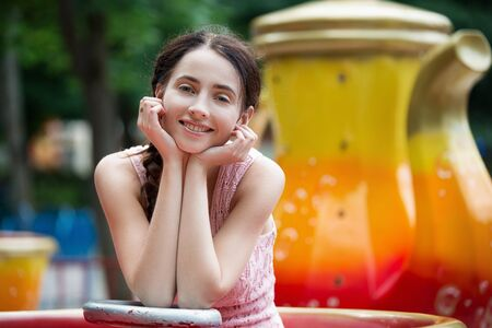 Attractive happy smiling girl in an amusement park sitting on carousel