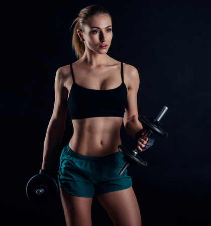 Cute athletic model girl in sportswear with dumbbells in studio against black background. Ideal female sports figure. Fitness woman with perfect sculpted muscular and tight body Stock Photo