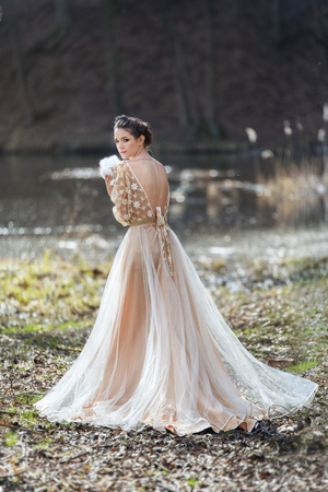 Portrait of woman wearing elegant dress standing near the lake with rabbit in hands Stock Photo