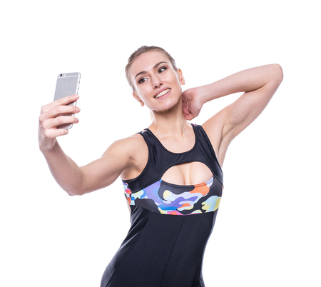 Happy fitness young woman wearing sportswear tracksuit is taking selfie with her mobile phone isolated on white background