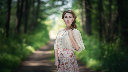 Portrait of pretty young woman walking in a fairy forest with bouquet of flowers Stock Photo