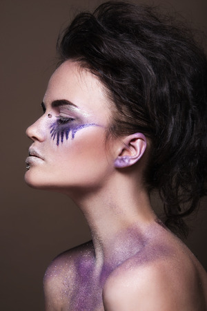 Fashion model with colorful make-up and blue glitter and sparkles on her face and body