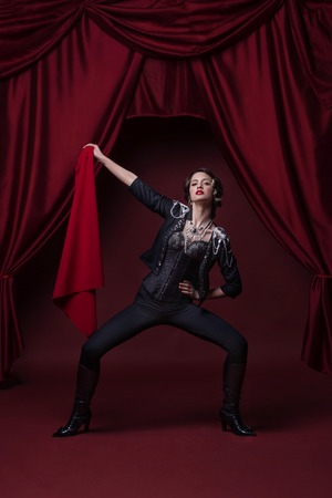 赤いカーテンで舞台にファッションの若い女性のアート写真