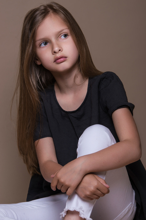 Portrait of cute little girl with dark hair in studio over beige background