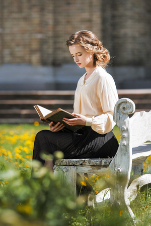 Retro portrait of a beautiful dreamy girl reading a book outdoors. Soft vintage toning