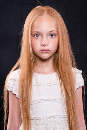Closeup portrait of cute little girl with redhead hair in studio over dark background