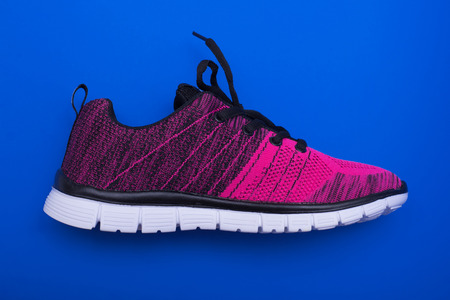 athletic wear: Pink and black sport woman shoes isolated on blue background Stock Photo