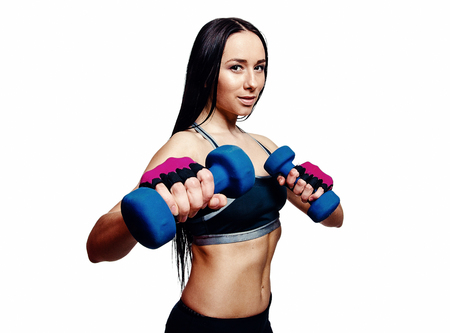 Beautiful young woman do exercises with dumbbells in studio. Sporty athletic girl lifting up weights against white background
