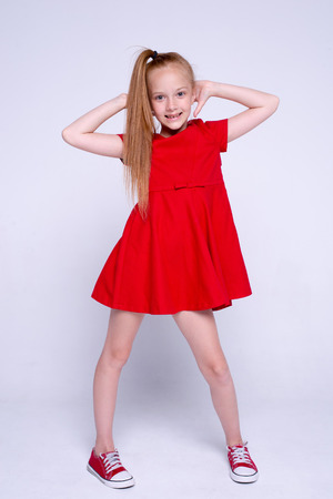 Beautiful little redhead girl in red dress and sneakers posing like model on white background