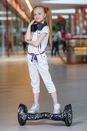 Happy and smiling girl rides on mini segway in the headphones at trading mall. Teenager riding on hover board or gyroscooter and listening to music