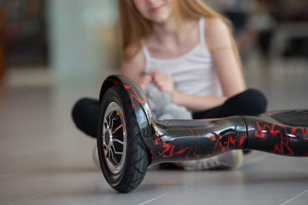 Happy and smiling girl with mini segway and plush bear doll at trading mall. Teenager riding on hover board or gyroscooter Stock Photo