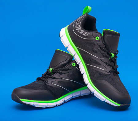 Pair of lime green and black sport unisex shoes isolated on blue background Stock Photo