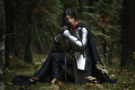 신비한 숲에서 chainmail과 갑옷을 입고 검을 들고 아름다운 전사 소녀