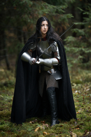 A beautiful warrior girl with a sword wearing chainmail and armor in a mysterious forest