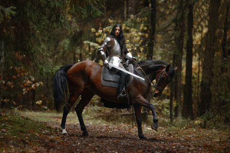 A beautiful warrior girl with a sword wearing chainmail and armor riding a horse in a mysterious forest Archivio Fotografico