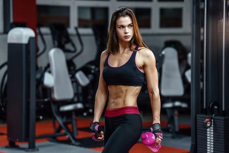 Giovane donna atletica dopo l'allenamento duro in palestra. La ragazza di forma fisica tiene lo shaker con nutrizione sportiva Archivio Fotografico - 89755842